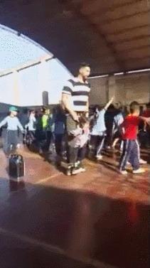 Учитель помогает девочке с инвалидностью потанцевать вместе  со всеми